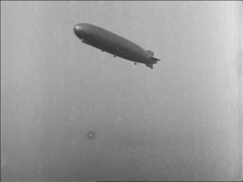 vídeos y material grabado en eventos de stock de low angle long shot graf zeppelin flying in sky / documentary - 1928