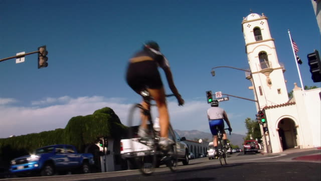 low angle long shot group of cyclists riding in a line past church on busy street - meno di 10 secondi video stock e b–roll