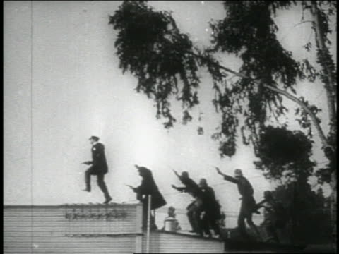 B/W 1914 low angle long shot PAN group of Keystone Kops running across rooftop / feature