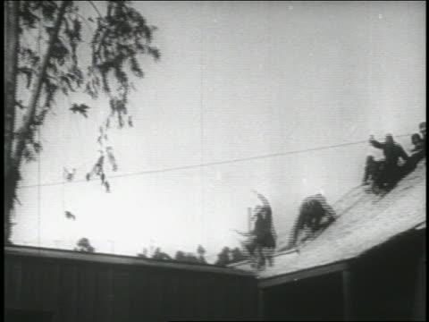 b/w 1914 low angle long shot pan group of keystone kops sliding down roof + running across rooftop - 1914年点の映像素材/bロール
