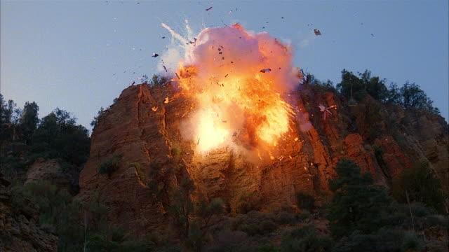 vídeos de stock, filmes e b-roll de low angle long shot helicopter exploding on side of mountain - set de filme