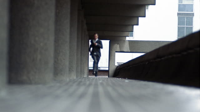 low angle long shot man running past columns towards cam (alternating slow to fast motion) - fuggire video stock e b–roll