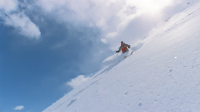 low angle long shot man skiing down slope / causing snow to tumble down slope behind him / breckenridge, colorado - real time stock videos & royalty-free footage