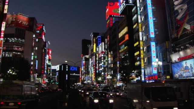 low angle long shot neon signs and billboards / tilt down busy street in shinjuku at night / tokyo, japan - 2005年点の映像素材/bロール
