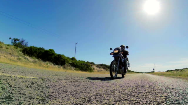 low angle long shot of biker on road/ western cape/ south africa - バイカー点の映像素材/bロール