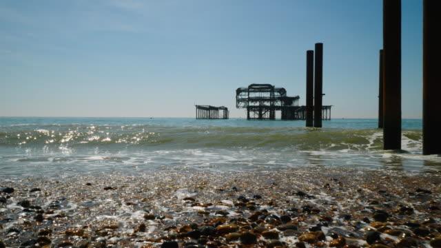 low angle long shot of the derelict west pier on brighton beach, uk. - kiselsten bildbanksvideor och videomaterial från bakom kulisserna