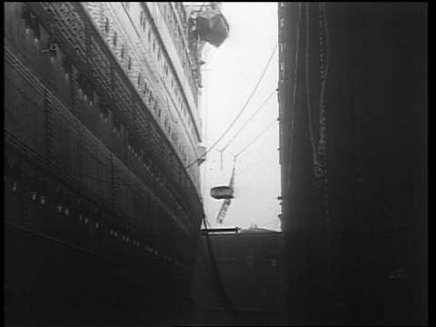 B/W 1933 low angle long shot pallet of crates being lowered on rope from large ship / end of Prohibition