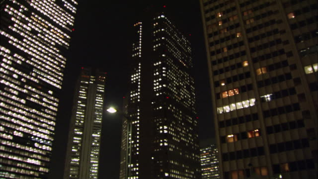 low angle long shot pan lights on in windows of office buildings at night / west shinjuku, tokyo, japan - 法人ビジネス点の映像素材/bロール