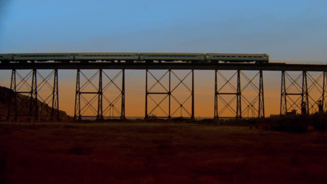 low angle long shot passenger train passing on bridge at sunset / field in foreground - long stock videos and b-roll footage