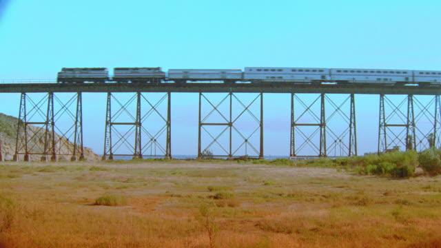 low angle long shot passenger train passing on bridge / field in foreground - whatif点の映像素材/bロール