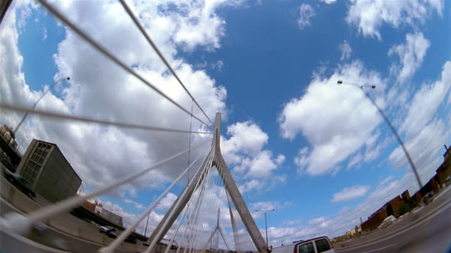 vídeos y material grabado en eventos de stock de low angle long shot point of view driving across leonard p. zakim bunker hill bridge with clouds in blue sky overhead / boston - puente leonard p. zakim bunker hill