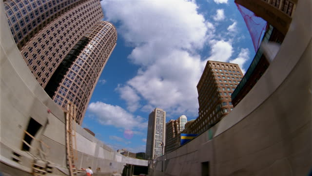 low angle long shot point of view driving down street with clouds in blue sky overhead / going through tunnel / boston - fischaugen objektiv stock-videos und b-roll-filmmaterial