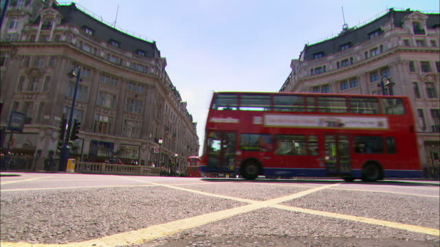 low angle long shot red double-decker buses crossing oxford circus / london - bus stock videos & royalty-free footage