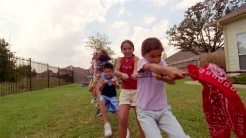 vídeos y material grabado en eventos de stock de low angle long shot swish pan children playing tug of war in backyard and winning - cuerda