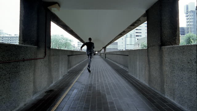 low angle long shot swish pan man running along ramp past cam - swish pan stock videos & royalty-free footage