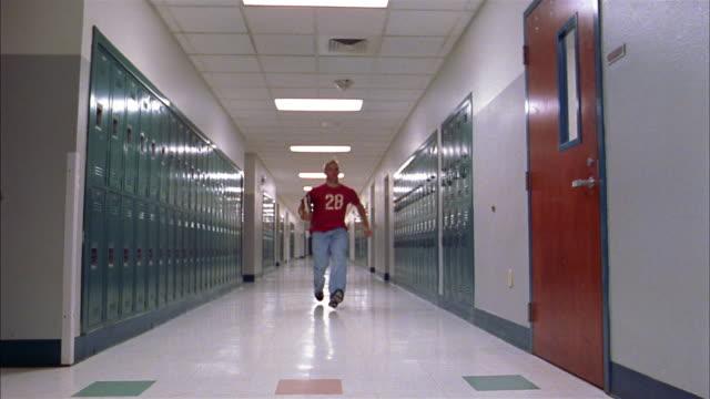 Low angle long shot teenage boy running in hallway / entering classroom