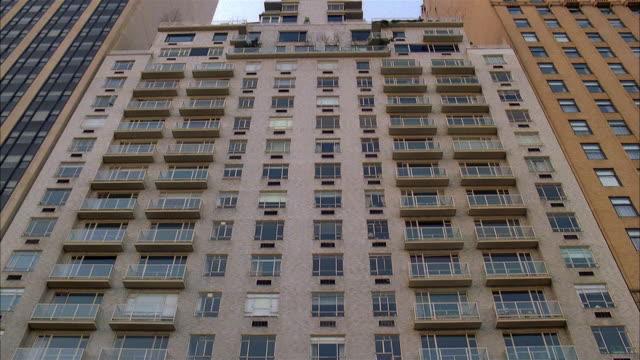 low angle long shot tilt up exterior of hi-rise apartment building / new york city - establishing shot stock videos & royalty-free footage