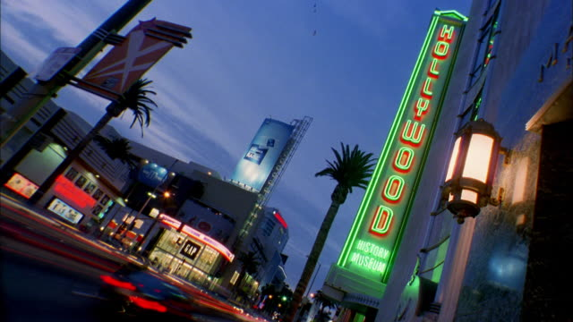 low angle long shot time lapse hollywood boulevard w/hollywood wax museum in foreground - boulevard video stock e b–roll