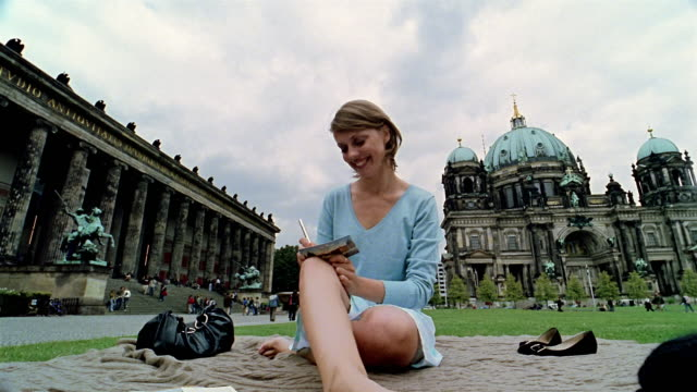 vídeos y material grabado en eventos de stock de low angle long shot woman sitting on lawn in front of berlin cathedral (berliner dom) writing postcard - capital letter