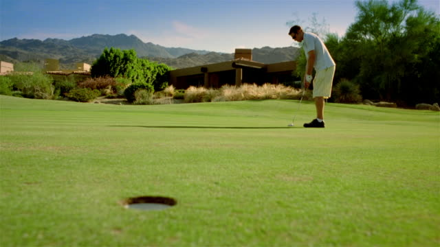 low angle long shot young man putting / missing hole and - palm springs california stock videos & royalty-free footage