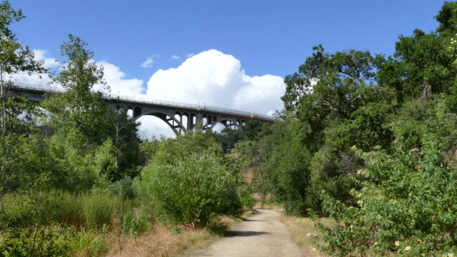 vidéos et rushes de low angle looking up at a large arch bridge from a dirt path pasadena arroyo seco - low angle view