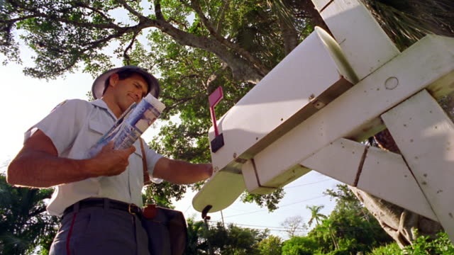 vídeos de stock e filmes b-roll de low angle ms mailman delivering + picking up mail from mail box - letterbox