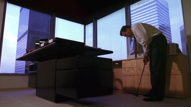 low angle male business executive putting golf ball beside desk in his office - golf video stock e b–roll