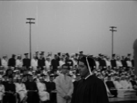 b/w 1965 low angle pan male graduate accepting diploma + shaking hands with men at podium / documentary - diploma stock videos and b-roll footage