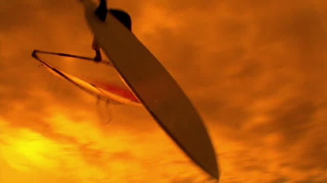 stockvideo's en b-roll-footage met orange low angle pan male windsurfer jumping over wave + doing flip in air / hawaii - windsurfen