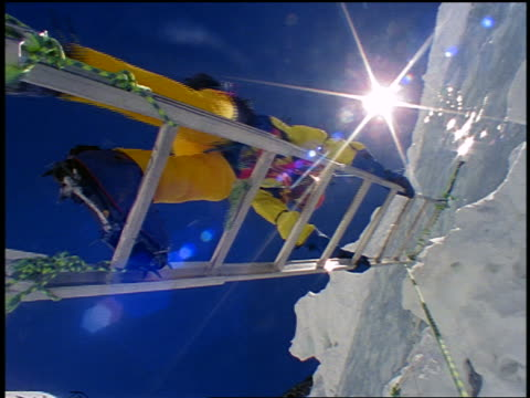 low angle man climbing ladder up wall of ice / mt everest expedition / himalayas - mount everest stock-videos und b-roll-filmmaterial