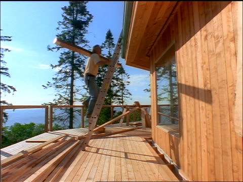 low angle man climbing up ladder to roof of house under construction carrying lumber - timber stock videos & royalty-free footage