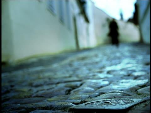 vídeos de stock, filmes e b-roll de blue blurry low angle man in black running to camera on narrow cobblestone street / prague, czech republic - foco difuso