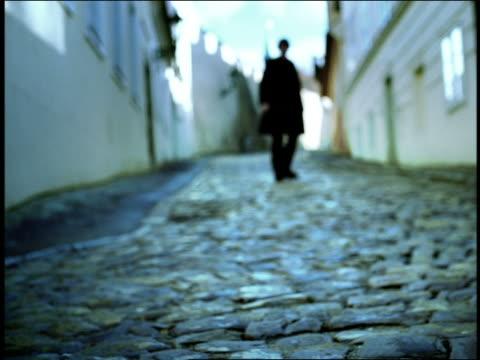 blue blurry low angle man in black walking on narrow cobblestone street / prague, czech republic - praga video stock e b–roll