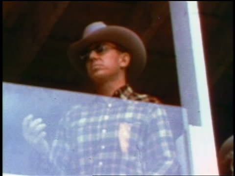 1957 low angle man in cowboy hat + sunglasses standing behind plexiglass / feature - 1957 stock videos & royalty-free footage
