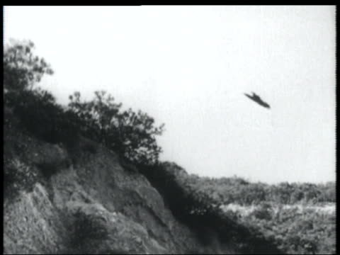 b/w 1952 low angle pan man in flying suit flying over hills - 1952 stock videos & royalty-free footage