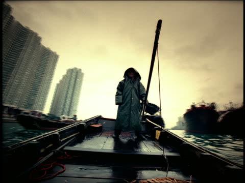 vidéos et rushes de high contrast low angle man in hooded raincoat steering boat + gesturing / skyscrapers in background / hong kong - image contrastée