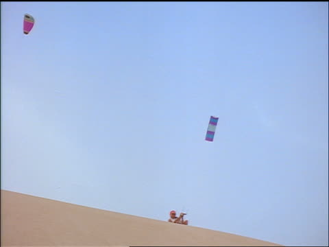 low angle pan man kite sailing buggy off of steep sand dune / buggy falls + man glides to ground / africa - dune buggy stock videos and b-roll footage
