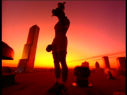 low angle man lifting dumbbells on roof at sunset / centrust tower in background / miami - arm curl stock videos and b-roll footage