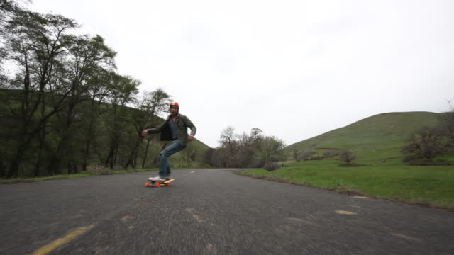 low angle, man longboards down hill - helmet stock videos & royalty-free footage