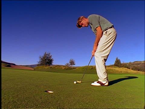 vídeos de stock, filmes e b-roll de low angle man putts golf ball into hole / raises arm in victory - camisa pólo