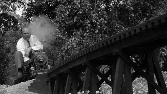 B/W 1951 low angle man riding mini steam train over bridge