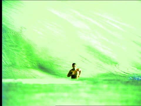 vídeos de stock e filmes b-roll de green low angle pan man running towards camera up sand dune - super exposto