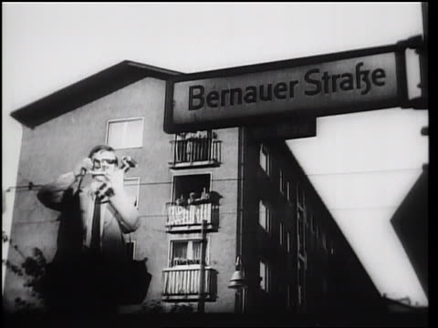 vídeos de stock, filmes e b-roll de b/w 1961 low angle man taking photograph standing next to bernauer strabe street sign / berlin - placa de nome de rua