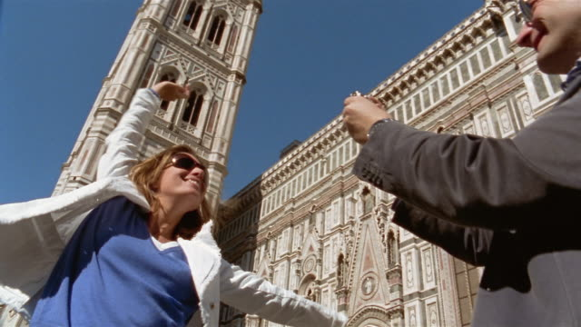 low angle man taking photos of woman posing near the basilica di santa maria del fiore in the piazza del duomo / florence, italy - fiore stock videos & royalty-free footage