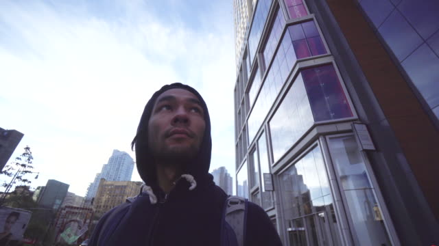 low angle, man walks down sidewalk in new york city - figura maschile video stock e b–roll