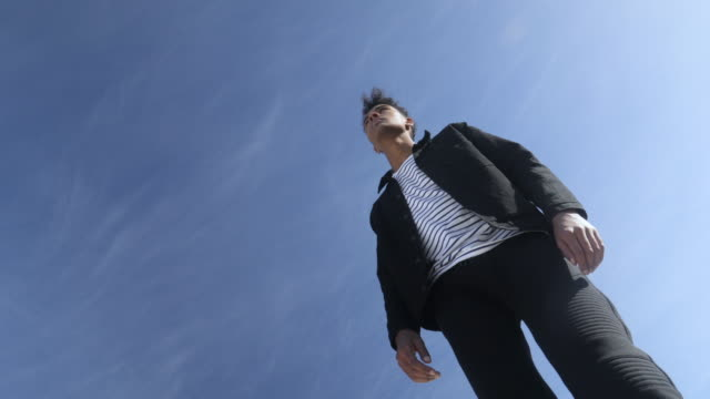 low angle, man wearing black jacket jumps - disinvolto video stock e b–roll