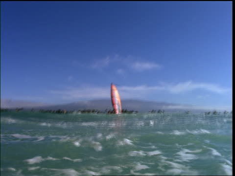 stockvideo's en b-roll-footage met low angle man windsurfing (laird hamilton) on ocean + jumping over camera - windsurfen