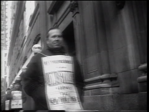 low angle man with sandwich board walking past camera in picket line / newspaper strike / nyc - newspaper strike stock videos & royalty-free footage