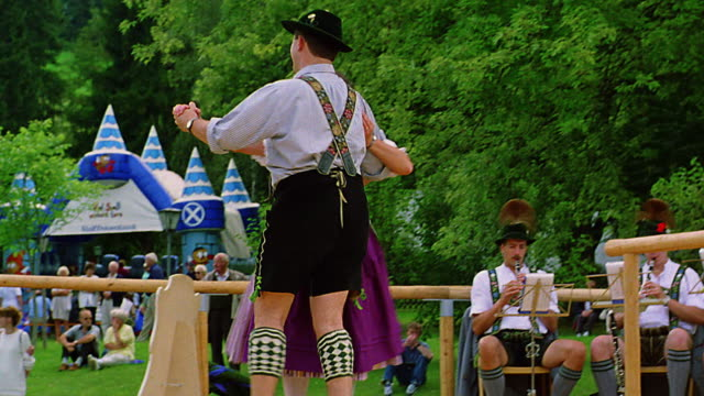 low angle man + woman in german costumes dancing on stage in park / bad kohlgrub, bavaria, germany - traditional clothing stock videos & royalty-free footage