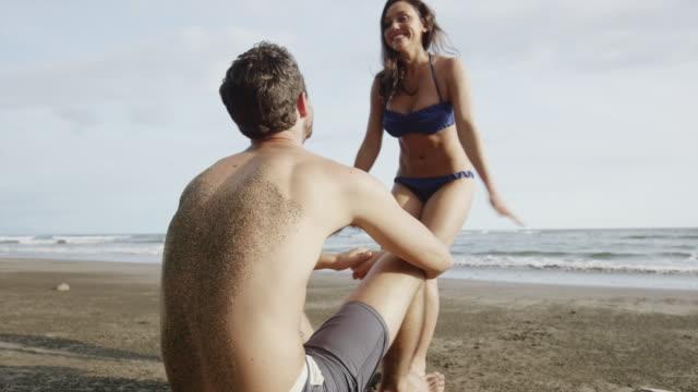 low angle medium panning shot of couple kissing on beach / esterillos, puntarenas, costa rica - sand bildbanksvideor och videomaterial från bakom kulisserna